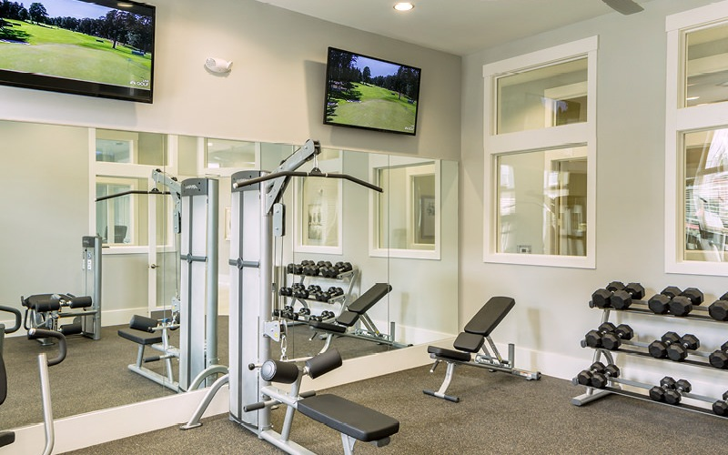 Fitness center has plenty of exercise equipment and mirrors